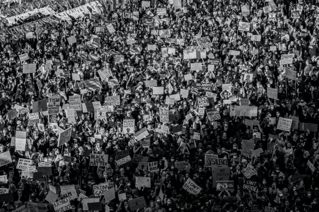Black and white image of a crowd of people holding BLM signs